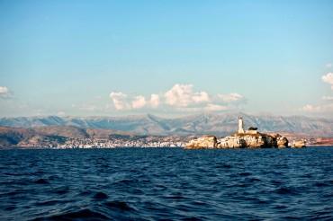 La proximité entre la Grèce et l'Albanie est étonnante. Pourtant, un monde les sépare. Au premier plan, le dernier îlôt rocheux grec. En arrière plan, les montagnes albanaises et la ville de Saranda © Philippe Henry / OCEAN71 Magazine
