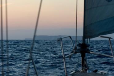 Après avoir navigué durant de longues heures de nuit, l'île de Lampedusa apparaît dans notre étrave © Philippe Henry / OCEAN71 Magazine