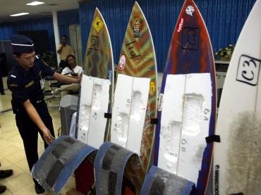 Un douanier inspecte les planches de surf utilisées par le brésilien Rodrigo Gularte pour dissimuler 6 kilos de cocaine en 2004. (AP Photo/Dita Alangkara)