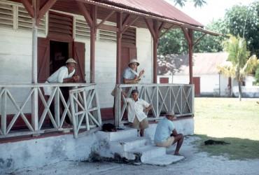 Diego Garcia, Tally House, 1968. Assis sur les escaliers, tournant légèrement le dos à l'objectif, se trouve Michel Vincatassin. Pressé par les autorités d'embarquer dans un des derniers navires à destination de l'île Maurice, Michel Vincatassin a eu la bonne idée de faire établir un papier officiel établissant son origine : l'archipel des Chagos. C'est ce même document qui fera la différence devant les tribunaux dix ans plus tard, permettant ainsi de négocier un important montant que les déportés chagossiens se partageront. @ DR
