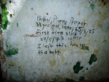 """Pierre Prosper Hidini est revenu visiter l'île sur laquelle il est né. Il y a laissé une trace touchante de son passage. """"J'ai quitté cette maison quand j'étais un bébé"""" a-t-il écrit sur les murs de son ancienne demeure. © Michael Barzam"""