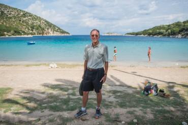 """John Crawshaw pose devant la baie qui sert de port au village d'Aréthuse. Selon l'hypothèse de l'équipe """"Odysseus Unbound"""", il s'agirait en fait de la mythique baie de Phorkys par où Ulysse serait arrivé © Philippe Henry / OCEAN71 Magazine"""
