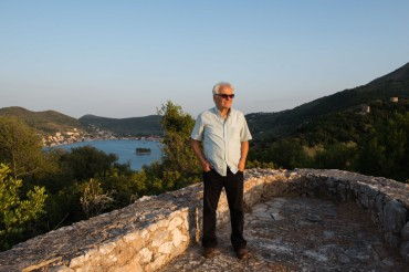 Former mayor of Ithaca, Spyros Arsenis stands on top of a watchtower with, behind him, a breathtaking view on Vathy and its bay © Philippe Henry / OCEAN71 Magazine