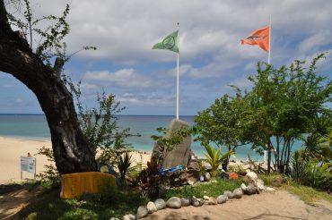 Devant le poste des maîtres-nageurs-sauveteurs de Boucan Canot, le fanion vert de surf est levé pour la première fois, autorisant les activités nautiques dans les filets. À ses pieds, une stèle à la mémoire de plusieurs victimes d'attaques de requin a été érigée © Andy Guinand / OCEAN71 Magazine