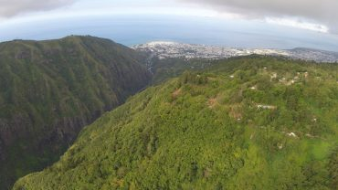 The steep slopes of Reunion Island are covered in lush vegetation. 40% of the territory is UNESCO protected. In the background, Saint-Denis, the capital. © Andy Guinand / OCEAN71 Magazine