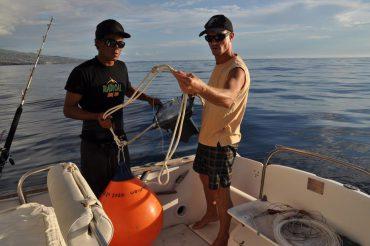 """Christophe Perry, dit """"Criquet"""" (à droite) nous montre une des smart drumlines. Le boîtier noir est la balise GPS alimentée par panneaux solaires. La ligne appâtée verticale est tenue par la bouée orange © Andy Guinand / OCEAN71 Magazine"""