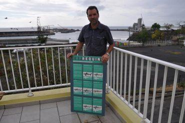David Guyomard, au Port, sur la côte ouest Réunionnaise. Il me présente un tableau qui aide à différencier les espèces de requins présentes dans les eaux de l'Océan Indien © Andy Guinand / OCEAN71 Magazine