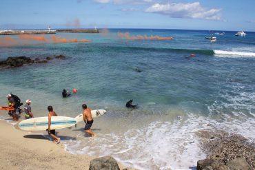 Lors d'un exercice aux Roches Noires, le dispositif des Vigies Requin Renforcées peut être admiré. Au large, les différents bateaux assistent. Dans l'eau et en binôme, les apnéistes accompagnent les derniers surfeurs. Les fumigènes avertissent d'un risque © Jo Besson / VRR