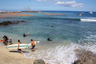 During an exercice at the Roches Noires beach, all of the Vigies Requin Renforcées program can be seen. In the background, the various boats assist the operations. The smoke bombs warn against a danger. The pairs of vigies bring the surfers back to shore and secure the area © Jo Besson / VRR