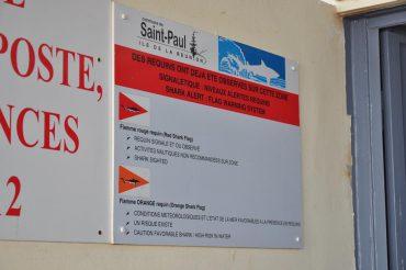 Sur le mur du poste des maîtres-nageurs sauveteurs des Roches Noires, l'explication des différents drapeaux du risque requin est affichée © Andy Guinand / OCEAN71 Magazine